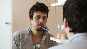Soltanto uomo di risveglio sonnolento torturato davanti allo specchio con uno spazzolino da denti nella sua bocca stock footage