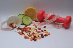 Soltar el peso con suplementos, pesa la elevación, frutas Imagenes de archivo