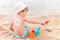Solteckningssunscreenen behandla som ett barn på (pojken) tillbaka. Royaltyfri Fotografi