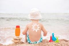 Solteckningssunscreenen behandla som ett barn på (pojken) tillbaka. Arkivbilder