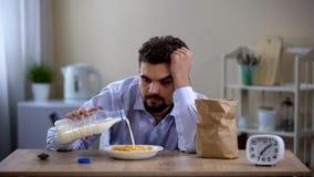 Soltero con exceso de trabajo soñoliento que come las avenas con leche por la mañana, cansancio imagenes de archivo