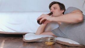 Soltero hermoso del hombre joven que come microprocesadores y que bebe la cerveza