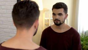 Soltero masculino joven que mira en espejo por la mañana, inseguridades del aspecto imagen de archivo libre de regalías