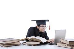 Soltero que estudia con el ordenador portátil y los libros 2 Imagen de archivo libre de regalías