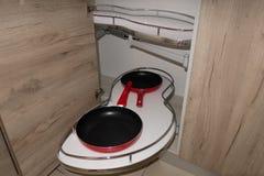 Solução para um armazenamento do canto da cozinha em um armário Uma unidade de canto com retirada arquiva para o cookware foto de stock