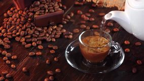 Soluble black coffee in small glass cup on a saucer stock video footage