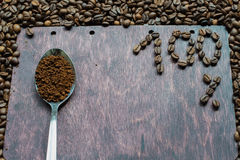 Soluble coffee in a spoon on wooden background. 100% natural coffee royalty free stock image
