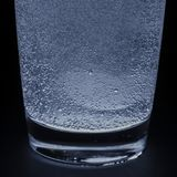 A soluble tablet dropped in a glass of water over dark background Royalty Free Stock Photography