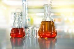 Solución anaranjada en frasco del cilindro del frasco en el CCB del laboratorio de ciencia Fotos de archivo