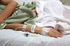 Solución salina en la mano de la mujer de los pacientes Fotografía de archivo