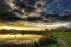 Soluppgång över dammet i höst Arkivfoto