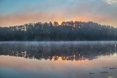 Soluppgång över den dimmiga sjön Royaltyfri Fotografi