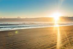 Soluppgång över den sandiga stranden för sned bolllägenhet på Ohope Whakatane royaltyfri foto