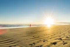 Soluppgång över den sandiga stranden för sned bolllägenhet på Ohope Whakatane arkivfoto