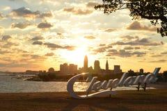 Soluppgång över det Cleveland tecknet och horisont på Lake Erie Edgewater parkerar Royaltyfri Bild