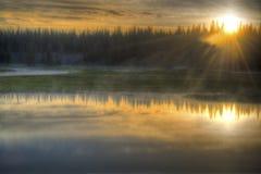 Soluppgång över en fridsam sjö i den Yellowstone nationalparken. Royaltyfri Fotografi