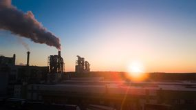 Soluppgång över fabriken Röken kommer från rören på gryning arkivfoton