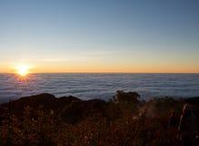 soluppgång över havet av molnet Arkivfoto