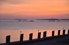 Soluppgång över havet med konturn av pir royaltyfri bild