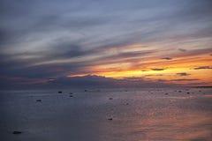 Soluppgång över havet med randiga moln Royaltyfria Bilder