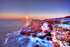 Soluppgång över havet och den steniga kusten Royaltyfri Bild