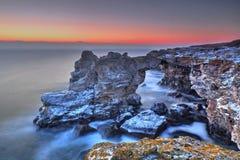 Soluppgång över havet och den steniga kusten Royaltyfria Foton