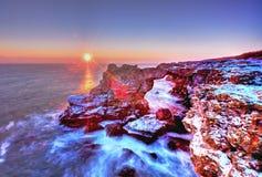 Soluppgång över havet och den steniga kusten Arkivbilder