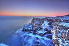Soluppgång över havet och den steniga kusten Arkivbild