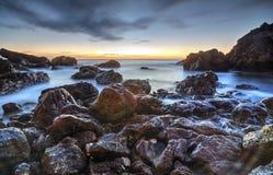 Soluppgång över havet och den steniga kusten Arkivfoton