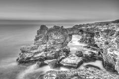 Soluppgång över havet och den steniga kusten på svartvitt Royaltyfri Fotografi