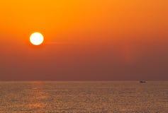 Soluppgång över havet och fiskebåten Arkivfoton