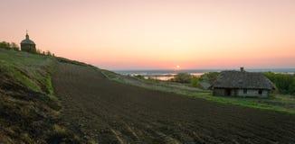 Soluppgång över jordbruks- land med odling, gammalt hus, träc royaltyfri fotografi