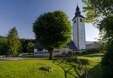 Soluppgång över kyrka av St John det baptistiskt på banken av Bohinj sjön, Bohinj, Slovenien, Europa arkivbilder