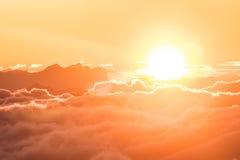 Soluppgång över molnen i fjällängarna Arkivfoto