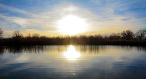 Soluppgång över sjön Arkivbild