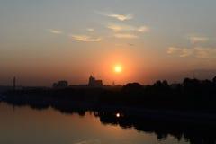 Soluppgång över staden och floden Arkivbilder