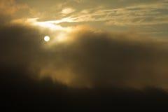 Soluppgång bak mörka moln Arkivbilder