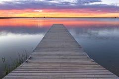 Soluppgång eller solnedgång över en fiskeskeppsdocka med färgrik molnrefle Arkivfoto