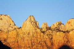 Soluppgång färgar i bergen, den Zion kanjonen Arkivfoto
