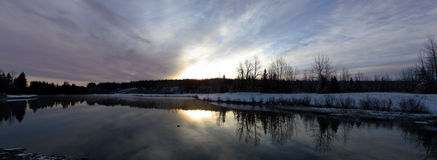 Soluppgång för molniga himlar för soluppgång över ett reflekterande damm Arkivfoton