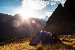 Soluppgång i bergen och tenten Arkivfoto