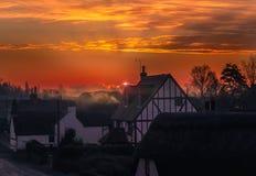 Soluppgång i byn av Monkton, Kent, UK Solen visas precis bak ett moln producera ett kantljus och en dimmig ogenomskinlighet royaltyfria foton