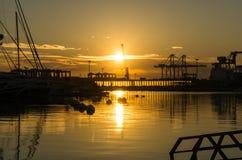 Soluppgång i hamnen av Valencia, solen stiger mellan anslöt segelbåtar, och lastport sträcker på halsen Royaltyfri Bild