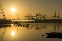 Soluppgång i hamnen av Valencia, solen stiger mellan anslöt segelbåtar, och lastport sträcker på halsen Royaltyfri Fotografi