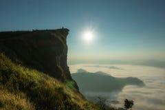Soluppgång i morgonen med ljus, signalljus i den dimmiga atmosfären som omges av berg Royaltyfria Foton