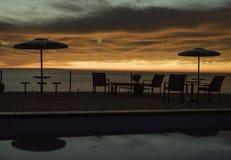 Soluppgång långt från simbassängen med guld- morgonmoln arkivfoto