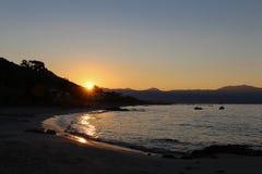 Soluppgång med en sikt från en sandig kust Arkivfoto