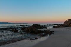 Soluppgång med en sikt från en sandig kust Royaltyfri Bild