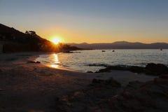 Soluppgång med en sikt från en sandig kust Royaltyfria Bilder