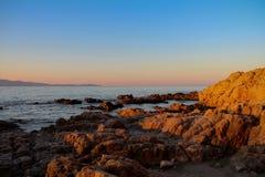 Soluppgång med en sikt på en stenig kust Arkivbilder